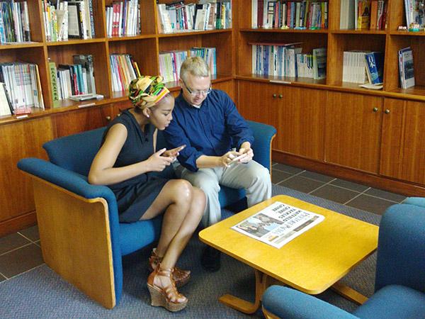 在南アフリカ共和国日本国大使館・広報文化センター内でスマートフォンを操作する、イノセントさん(左)とライアンさん(右)