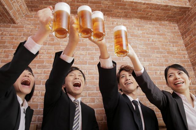 達成感があると忘年会のお酒もより美味しい? 写真:KAORU/PIXTA(ピクスタ)